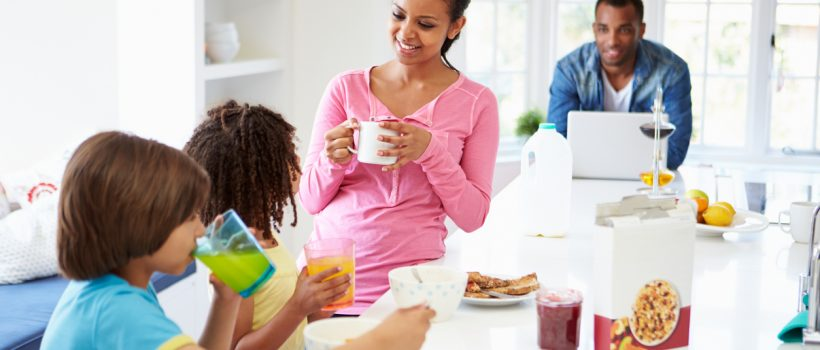 Family Having Breakfast In Kitchen Together