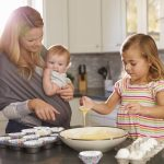 Young girl preparing cake mix in kitchen, mum showing baby